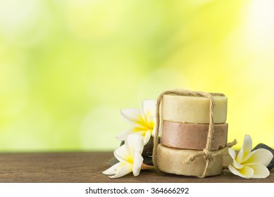 coconut soap, mangosteen soap, rice milk soap placed on a wooden table with frangipani and natural background. Spa concept.