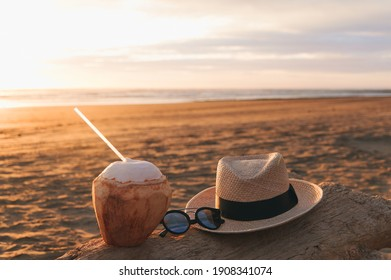A coconut, sunglasses and hat on a tree trunk on the beach in a beautiful sunset