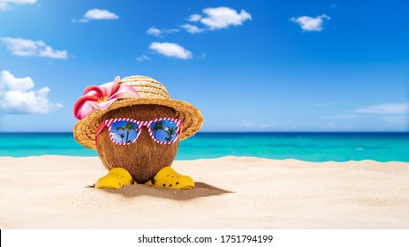 Coconut with sunglasses and Strawhat at tropical beach - Holiday Vacation Concept