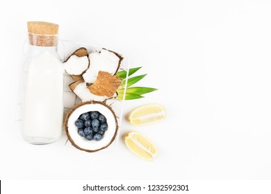 Coconut vegan milk in a bottle and coconuts on white background