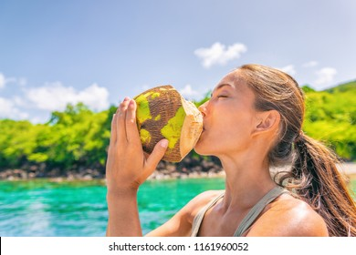 Coconut water Caribbean tropical food tourist woman drinking fresh natural from the coco on cruise ship travel vacation. Asian girl enjoying summer holidays.