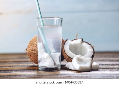 Coconut water in the composition with an open coconut with white flesh on a wooden background. Organic healthy dietary product widely used in cosmetology and Spa