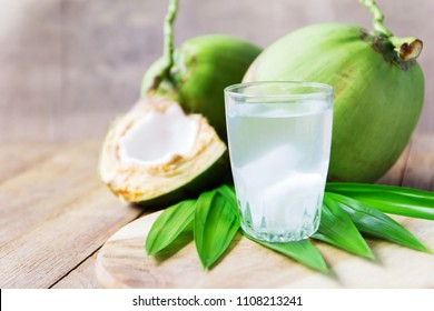 coconut water in glass on wooden board for drink.