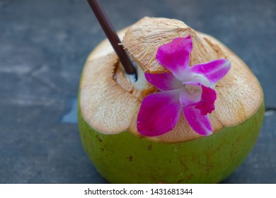 Thai​ coconut water and orchid on wooden table