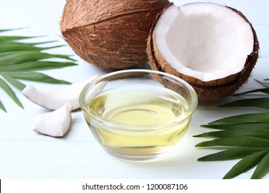 coconuts and coconut oil with tropical leaves on a wooden background