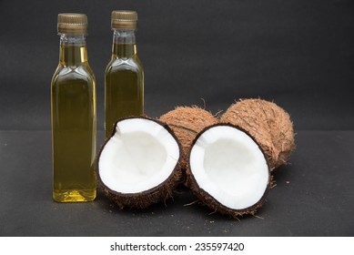 Coconuts cut in half and whole coconuts. Two bottles of coconut oil. Kerala India