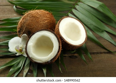 Coconuts with leaves and flower, on grey wooden background