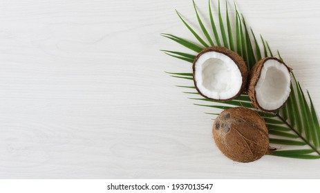 Coconuts with palm leaf on white wooden background. Tropical coconut fruit.