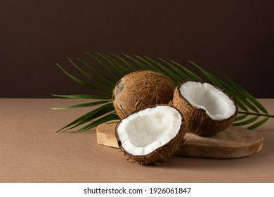 Coconuts with palm leaf over brown background. Tropical fruit.
