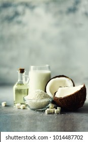Coconuts products - milk, oil, shavings on grey concrete background. Copy space. Hair, skin and body treatment