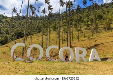 COCORA VALLEY / COLOMBIA - September 14, 2019: A women sits on the Cocora Valley sign on one of the trails in the park, Colombia, South America.