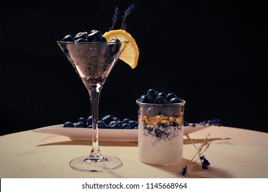 Coctail with bluberriy in martini glass on wooden table and black backgrouns