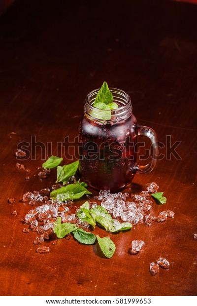 Coctail in a glass with black currant on wooden table