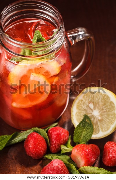 Coctail in a glass with raw fruit and lemon on wooden table