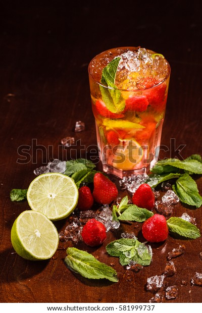 Coctail in a glass with raw fruit and lemon on wooden table with crashed ice and mint