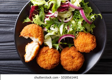 Cod cake in breading with fresh mix salad close-up on a plate. horizontal top view from above