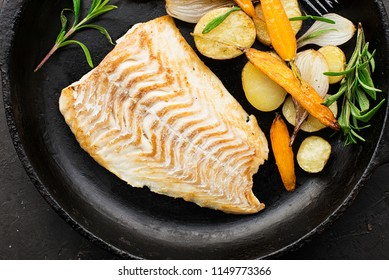 Cod fillet baked with fresh farmer's vegetables: potatoes, carrots, onions. Top View