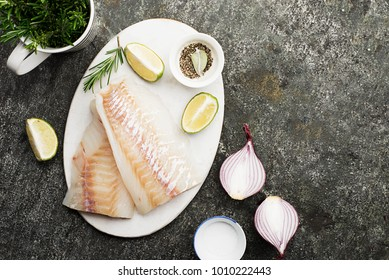 Cod fillet of cod fish with fresh vegetables: sweet pepper, rosemary, sweet red onion, ground pepper on a white cutting board on a grunge gray background. Top View