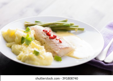 Cod fillet with mashed potatoes topped with some chili