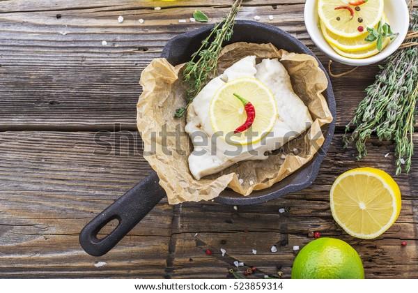 Dorschfilets, gebacken in Pergamentpapier mit Zitronenscheiben und einem Thymian auf leichten Speisen. Selektiver Fokus.Konzept der gesunden Ernährung.