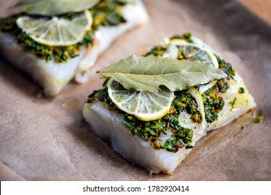 Cod fillets with coriander crust, lemon and bay leaf prepared for baking