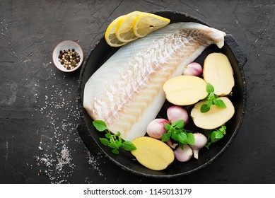 Cod fillets with fresh potatoes, shallots, basil, lemon in a black cast-iron frying pan on a dark background before cooking. Top View