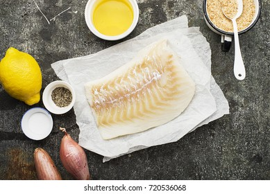 Cod fillets with melted butter and breadcrumbs before cooking in parchment paper. top view.