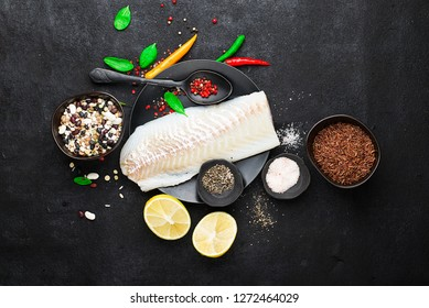 Cod fillets on a black ceramic plate for the preparation of a healthy dish with the addition of pink pepper, hot pepper, spinach, lemon, salt on a simple black background. Top view. Copy space.