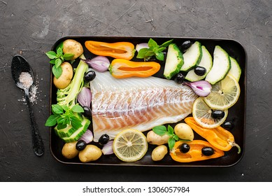Cod fillets of white fish with different organic farm vegetables, pepper, broccoli, onions, rosemary, basil, potatoes, zucchini on a baking sheet before preparation. Top View.