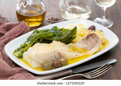 cod fish with cabbage, potato and olives on dish