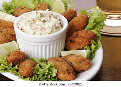"""Cod fish cakes (croquettes) with chunky tartar sauce. Typical dish made up of potatoes, codfish, eggs and parsley. Also known as """"Bolinhos de bacalhau"""" in Brazil or """"Pasteis de bacalhau"""" in Portugal."""