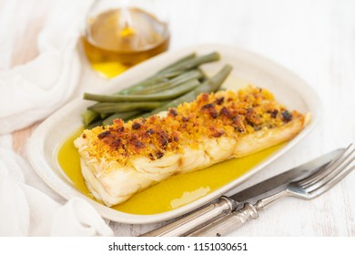 cod fish with corn bread and green beans on dish
