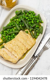 cod fish with green beans and peas on dish