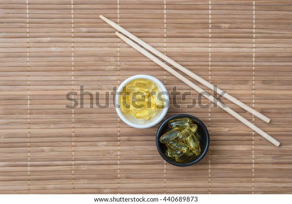 Cod liver oil omega 3 gel capsules and chopsticks on bamboo mat