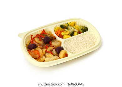 Cod a Portuguese style, rice and steamed vegetables in a tray for frozen food on a white background.