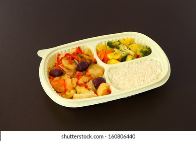 Cod a Portuguese style, rice and steamed vegetables in a package for frozing food. Package on a brown background.