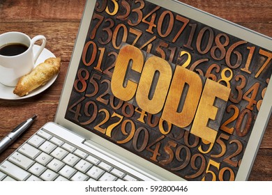 code word in vintage letterpress wood type against number background on a laptop computer with a cup of coffee