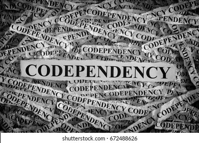 Codependency. Torn pieces of paper with the words Codependency. Concept Image. Black and White. Closeup.