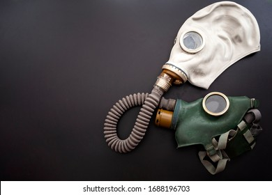 Codependent relationship, negative emotions, hazardous affair and toxic love concept with two gas masks connected on the same hose to represent codependency isolated on dark background with copy space