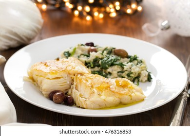 codfish with bread and spinach on white plate on brown wooden background