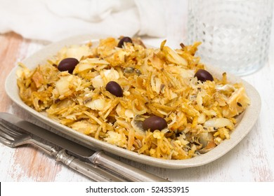 codfish with potato chips and olives on plate on white background