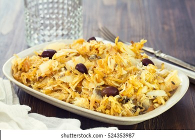 codfish with potato chips and olives on white plate