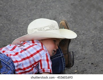 CODY, WYOMING - JULY 2, 2016 - young boy in cowboy hat laying on his mother's leg