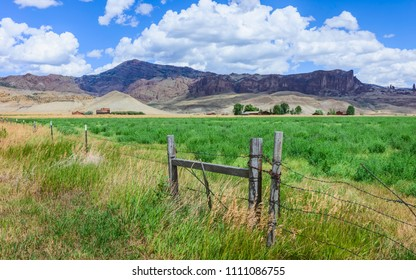 Cody, Wyoming, USA - Agriculture across the prairie and rugged undulating landscape of Buffalo Bill State park showing the rocky mountains and crops in the foreground near Cody, Wyoming, USA.