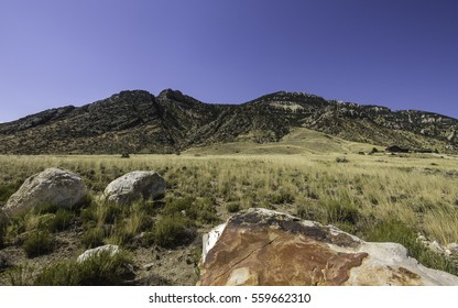 Cody, Wyoming, USA. The arid landscape of the prairie in late summer with view of foothills of Rocky Mountains with an isolated ranch house on a bright day near Cody, Wyoming, USA.