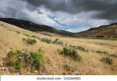 Cody, Wyoming, USA. The arid prairie with sagebrush, dry grassland, and Rocky Mountains and glimpse of greenery on a bright sunny day near Cody, Wyoming, USA.