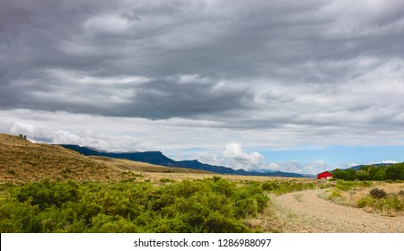 Cody, Wyoming, USA. Dirt road flanked by arid prairie and sagebrush with red barn on horizon and the Rockies in summer in Cody, Wyoming, USA.