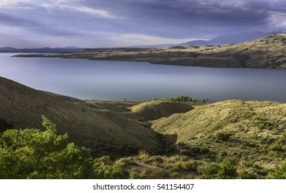 Cody, Wyoming, USA - View across the rugged undulating landscape of Buffalo Bill State park showing the reservoir, rocky mountains near Cody, Wyoming, USA.