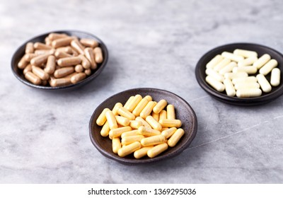 Coenzyme Q10, Alpha Lipoic Acid and Green Tea capsules. Immune system support. Concept for a healthy dietary supplementation. Bright stone background.