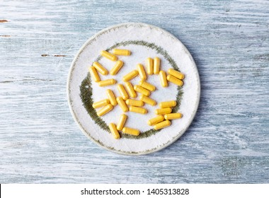 Coenzyme Q10 capsules. Dietary supplements. Rustic wooden background. Top view. Copy space.